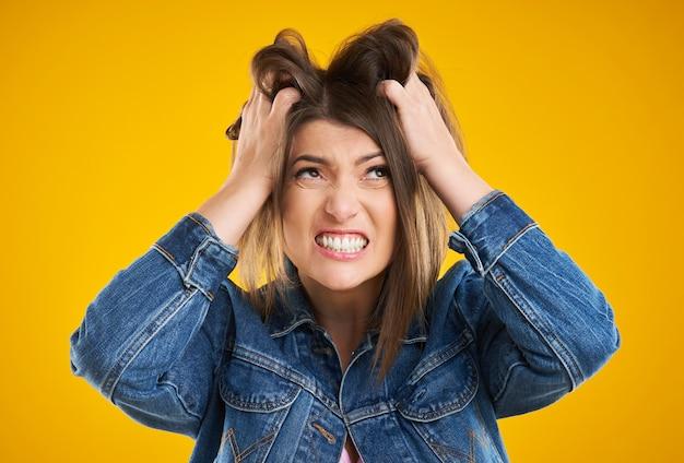 Malheureuse femme en veste en jean posant sur fond jaune
