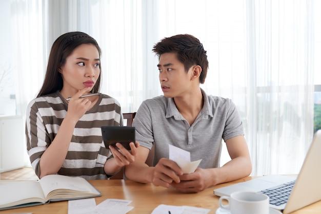 Malheureuse jeune famille calculant ses dépenses en faillite