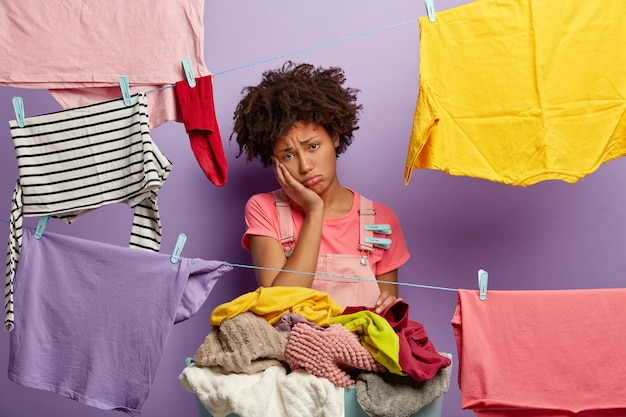 Malheureuse jeune femme avec un afro posant avec une lessive en salopette