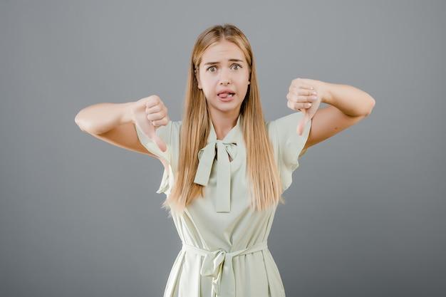 Malheureuse jeune femme déçue montrant thubms bas isolé sur gris