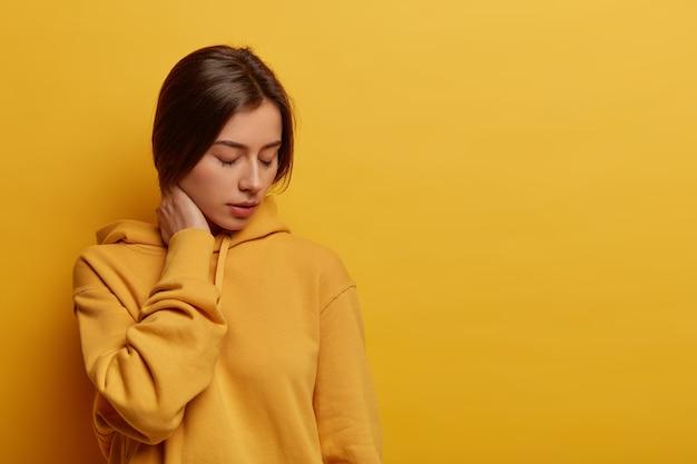 Malheureuse jeune femme en détresse se sent seule, touche le cou et regarde vers le bas, garde les yeux fermés, étant très épuisée