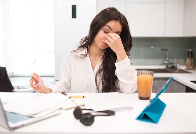Malheureuse jeune femme travaille la cuisine dans sa maison, elle est très fatiguée. mais encore beaucoup de travail. le travail à domicile est difficile et fatigant