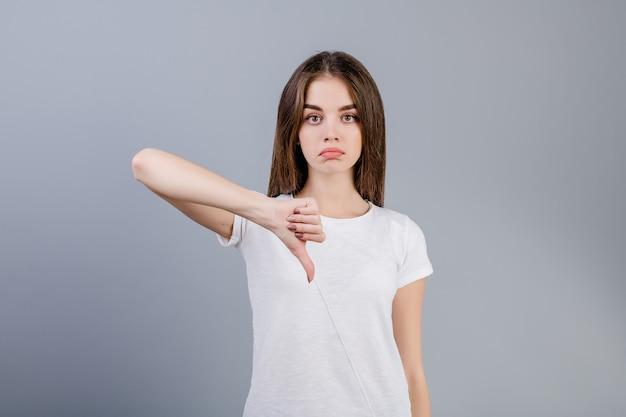 Malheureuse triste jeune femme montrant les pouces vers le bas isolé sur gris