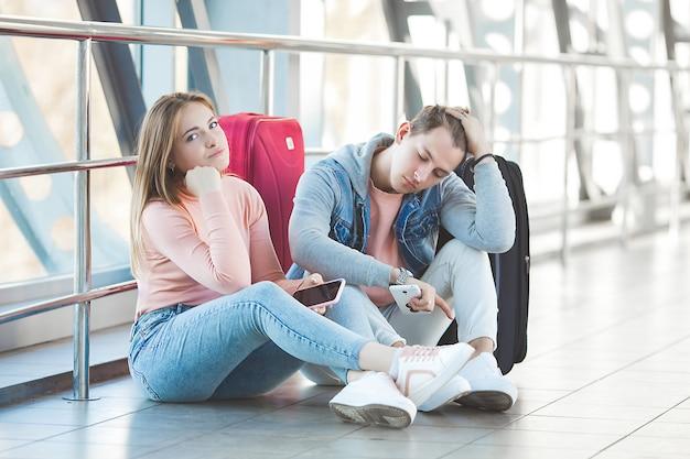 Malheureux couple attendant à l'aéroport leur vol retardé. les jeunes ont raté leur train. homme et femme à l'aéroport.