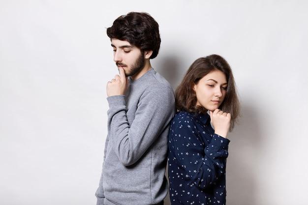 Malheureux couple debout dos à dos tenant leurs mains sur le menton regardant vers le bas ayant des expressions réfléchies