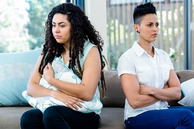 Malheureux couple de lesbiennes assis sur un canapé dans le salon