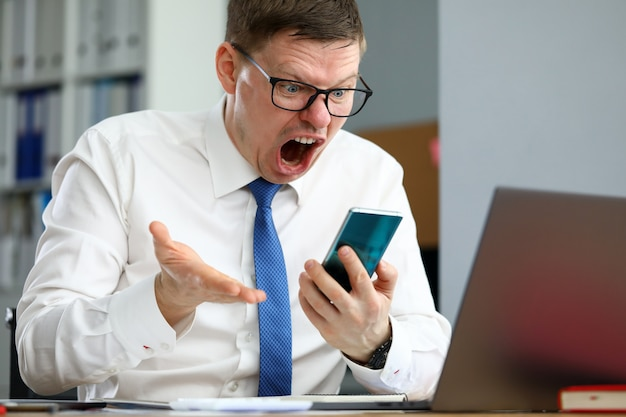 Malheureux homme d'affaires assis à la table de travail criant au portrait de téléphone mobile. mauvaise nouvelle et prévisions négatives ou accord non rentable au concept de bourse en ligne
