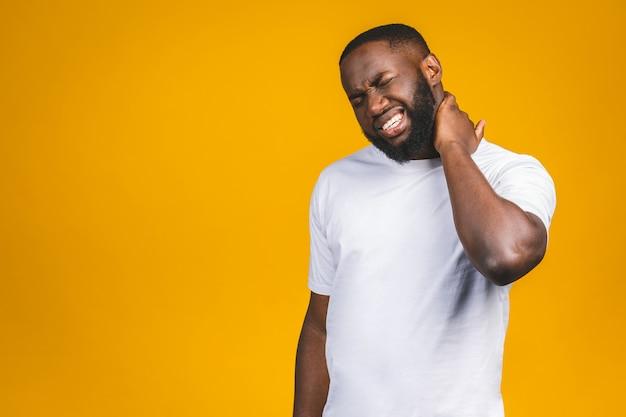Malheureux jeune bel homme afro-américain avec une douleur au cou vraiment mauvaise, après de longues heures de travail, étudier, mur blanc isolé. émotions humaines négatives, expressions faciales.