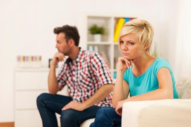 Malheureux jeune couple assis dans le salon