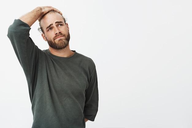 Malheureux jeune homme avec une coiffure à la mode et une barbe tenant la tête avec la main