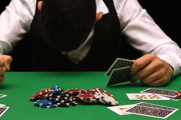Malheureux jeune homme se sentant triste, désespéré et stressé après avoir perdu son argent en jouant au poker et au blackjack dans un casino nocturne. espace de copie