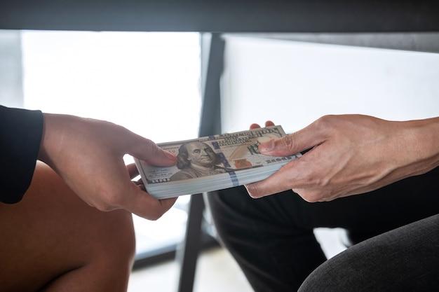 Malhonnêteté en matière de fraude dans les affaires, homme d'affaires reçoit des pots-de-vin sous table aux gens d'affaires pour donner le succès au contrat d'investissement, concept de corruption