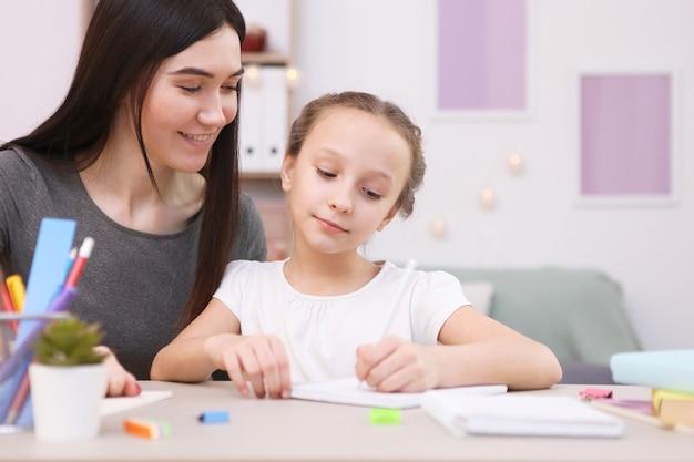 Maman aide la fille à faire ses devoirs enfants et parents