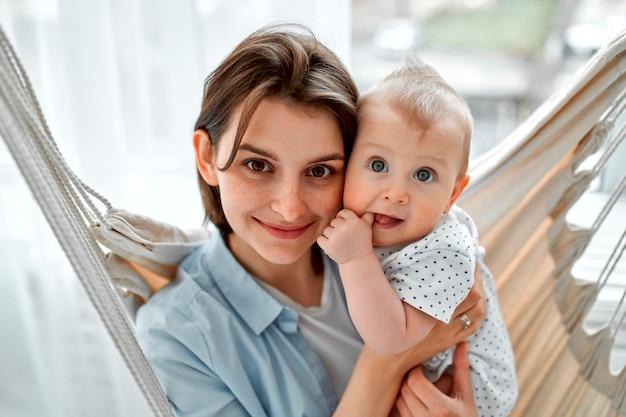 Maman aimante portant son nouveau-né à la maison. mère et enfant sur un hamac en filet. maman et petit garçon jouant dans une chambre ensoleillée. parent et petit enfant se détendre à la maison. famille s'amusant ensemble.