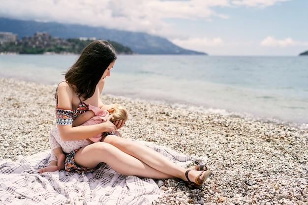 Maman allaite sa petite fille tout en la tenant à genoux sur la plage de galets
