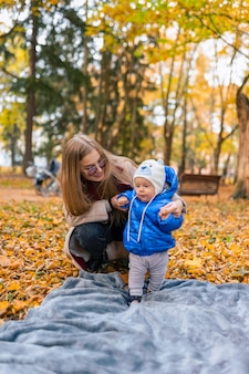 Maman apprend à l'enfant à marcher avec son bébé avec son aide