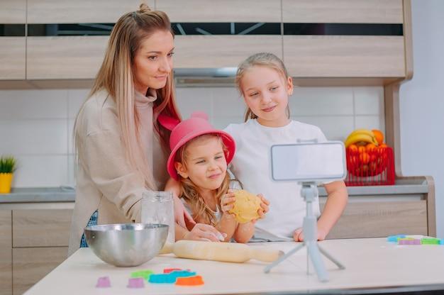 Maman apprend à ses filles à faire cuire de la pâte dans la cuisine.