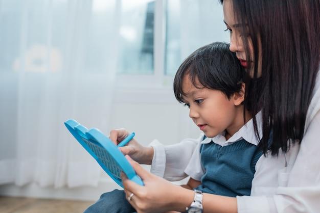 Maman asiatique enseignement garçon mignon à dessiner ensemble tableau noir