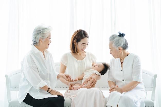 Maman asiatique tenant un bébé et deux femmes âgées