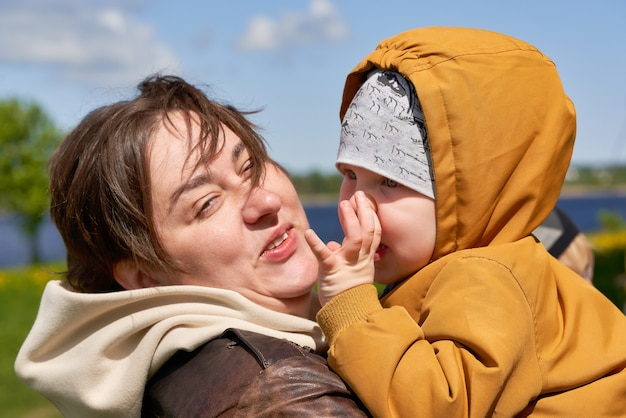Maman aux cheveux courts embrasse son petit fils en le tenant dans ses bras