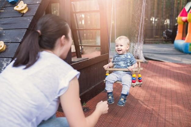 Maman balançant le petit garçon dans la balançoire à l'heure d'été. tout-petit avec sa mère s'amusant à l'extérieur dans le parc. concept de mode de vie familial heureux
