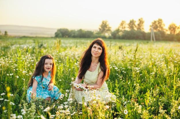 Maman avec bébé dans un champ de marguerites au coucher du soleil. tonifiant
