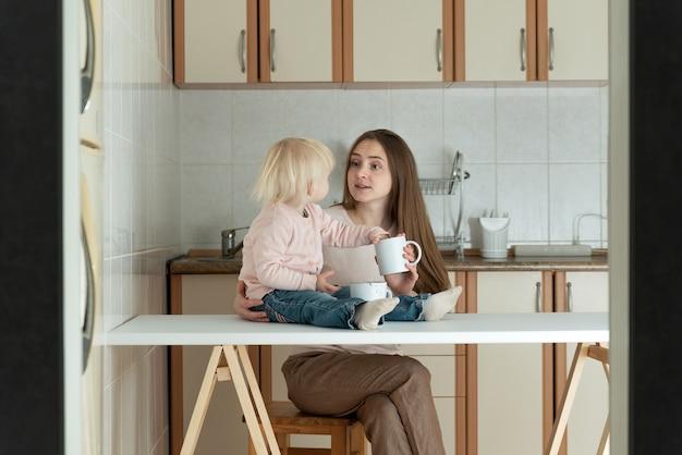 Maman et bébé dans la cuisine. jeune maman et enfant en bas âge prennent le petit déjeuner à la maison.