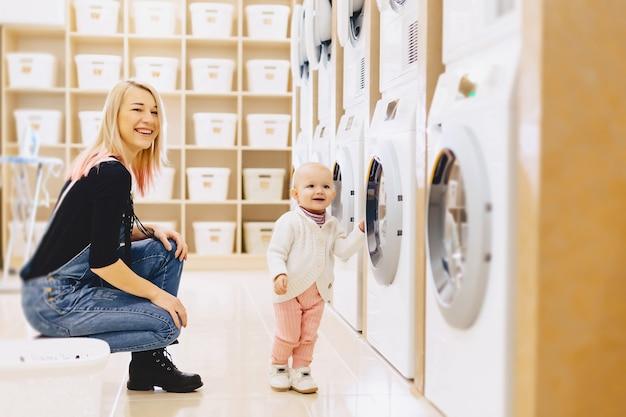 Maman et bébé dans la lessive prennent des choses et jouent