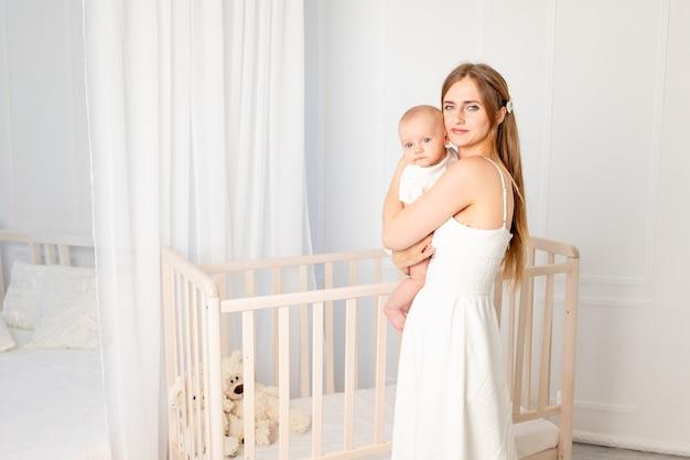 Maman avec bébé dans ses bras à la maison à la crèche de la crèche, le concept de famille et de maternité