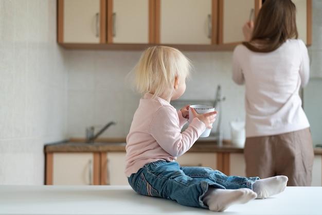 Maman et bébé de deux ans avec une tasse dans leurs mains dans la cuisine. petit déjeuner en famille