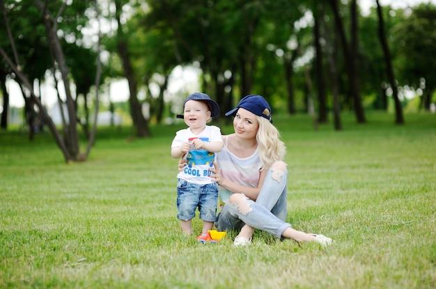 Maman et bébé fils avec des bouchons sur l'herbe verte