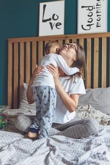 Maman et bébé s'amusent ensemble dans la chambre sur le lit