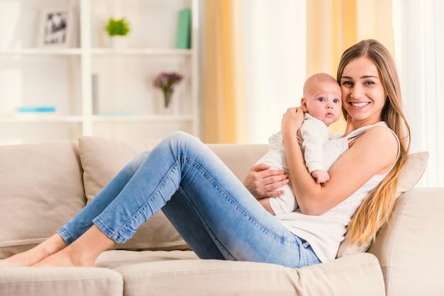 Maman et bébé sont assis sur le canapé et regardent devant.