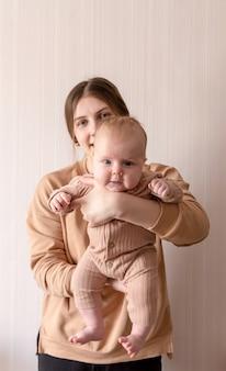 Maman et bébé en vêtements marron sur fond clair