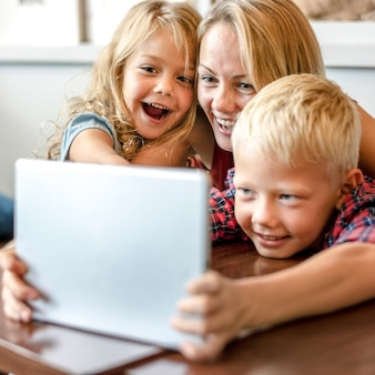 Maman blonde et enfants faisant un appel vidéo sur une tablette