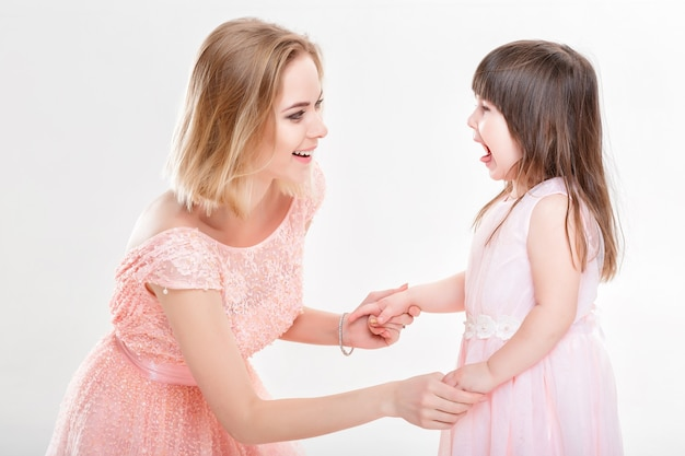 Maman blonde fille réconfortante en robes roses princesses sur fond gris. bébé pleure