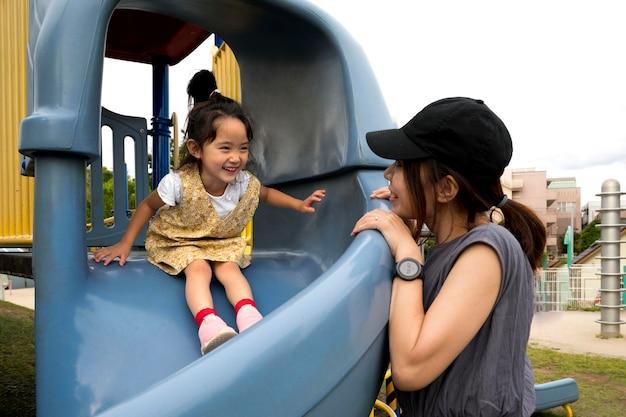 Maman célibataire jouant avec sa fille dans un parc