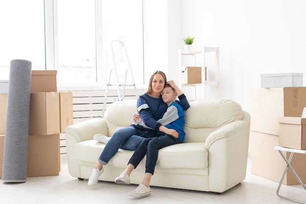 Maman célibataire mignonne et petit garçon se relaxant après le déménagement. le concept d'hypothèque de pendaison de crémaillère et la joie d'un nouveau logement.