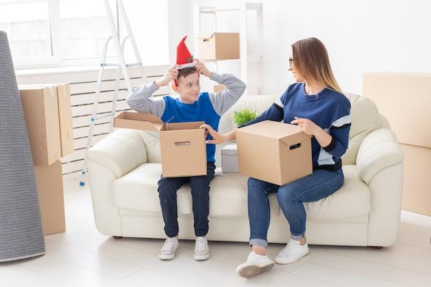 Maman célibataire mignonne et petit garçon trient des boîtes avec des choses après le déménagement