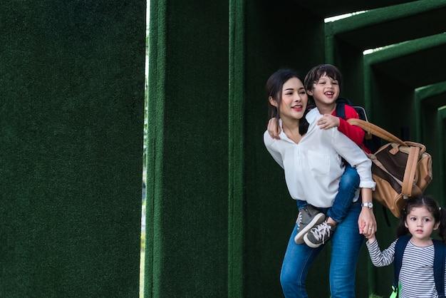 Maman célibataire portant et jouant avec ses enfants dans le jardin avec fond de mur végétalisé.