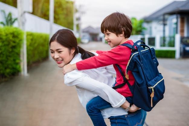 Maman célibataire portant et jouant avec ses enfants près de la maison avec le fond de rue de la villa.