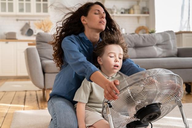 Une maman détendue et un petit enfant rafraîchissant s'assoient devant un grand ventilateur intérieur soufflant de l'air frais rafraîchissant à la maison