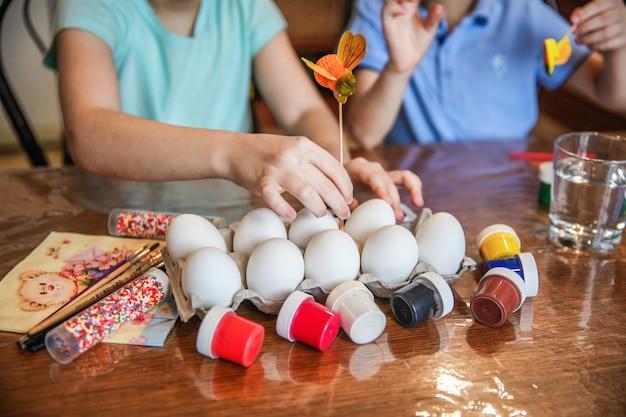 Maman avec deux enfants décorent les oeufs de pâques assis à la table à la maison dans la cuisine