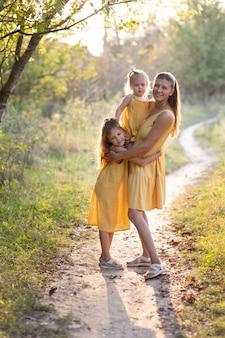 Maman et deux filles, un et sept ans dans la nature
