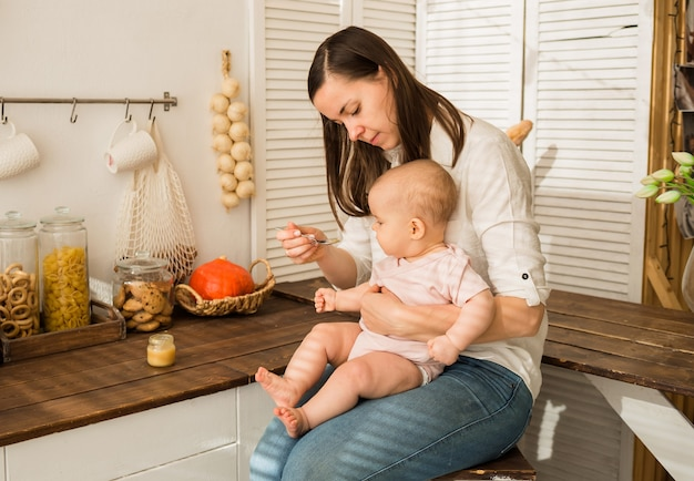 Maman donne de la compote de pommes à la petite fille dans la cuisine