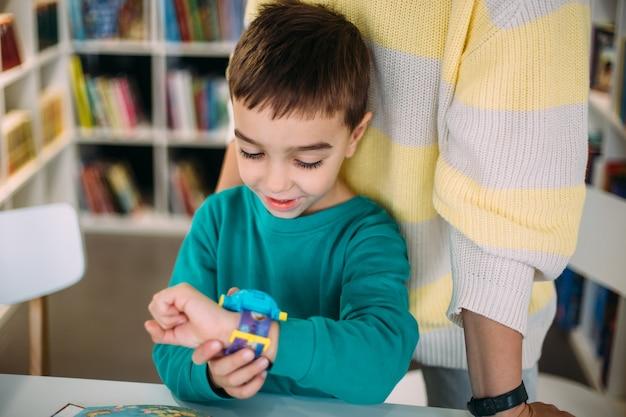 Maman donne à son fils sa première montre en apprenant à déterminer l'heure par l'horloge