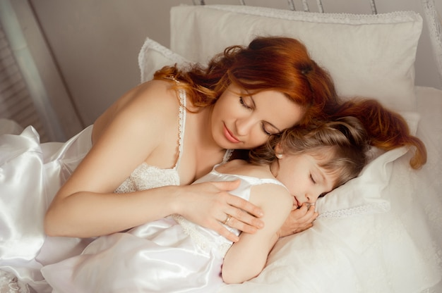 Maman dort à côté de sa fille. bébé qui dort.