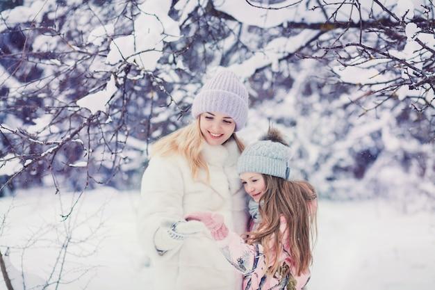 Maman élégante jouant avec petite fille mignonne