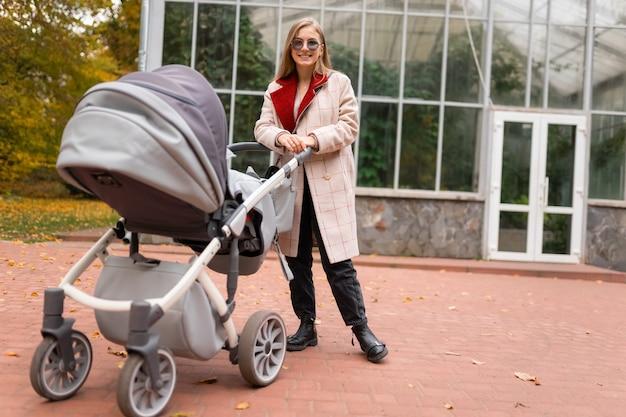 Maman élégante avec poussette dans le parc de l'automne