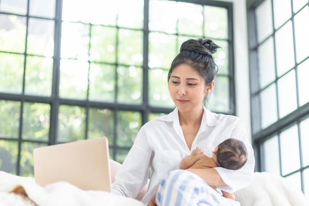 Maman élève un bébé alors qu'elle travaille à la maison.